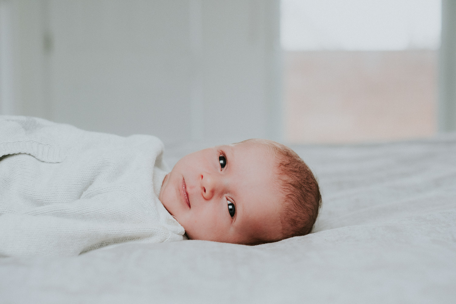 newborn baby boy with eyes open lying on bed natural light
