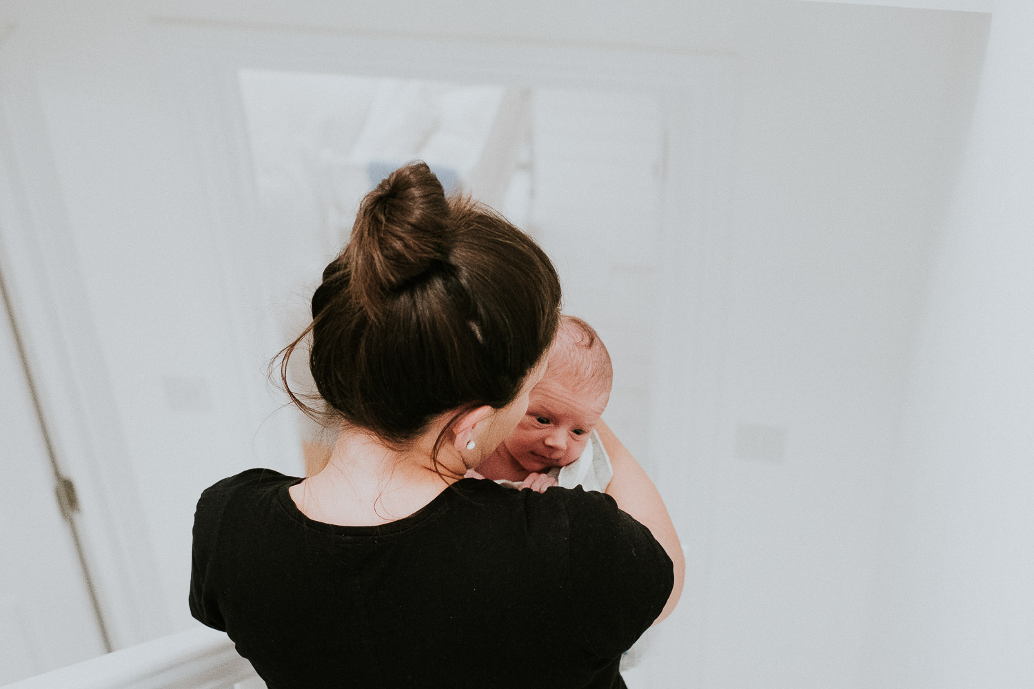 newborn baby boy being carried downstairs in mothers arms