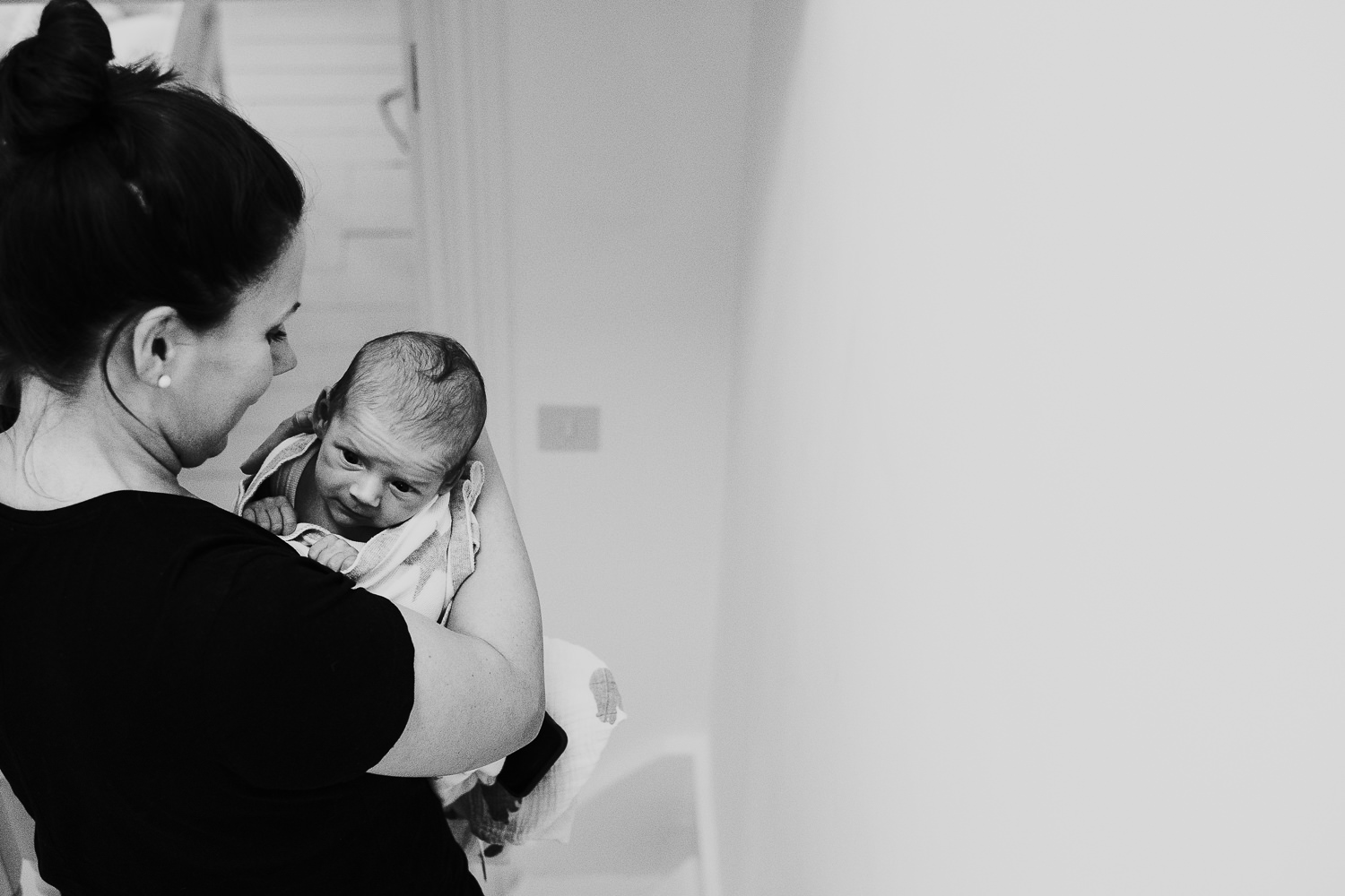 newborn baby boy being carried downstairs in mothers arms black and white photo