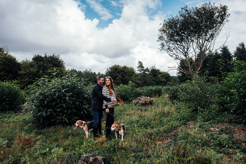 MATERNITY PHOTOGRAPHER LONDON AND KENT WOODLAND PHOTO OF COUPLE WITH DOGS