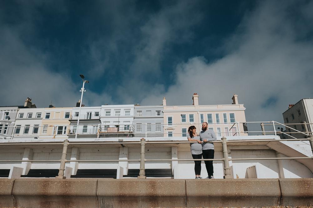 PREGNANT COUPLE ON BEACH PROMENADE HASTINGS MATERNITY PHOTOGRAPHER LONDON