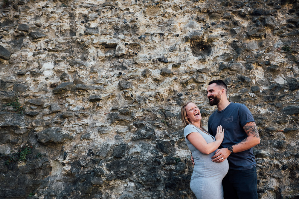 HEAVILY PREGNANT COUPLE LAUGHING AGAINST STONE WALL MATERNITY PHOTOGRAPHER LONDON