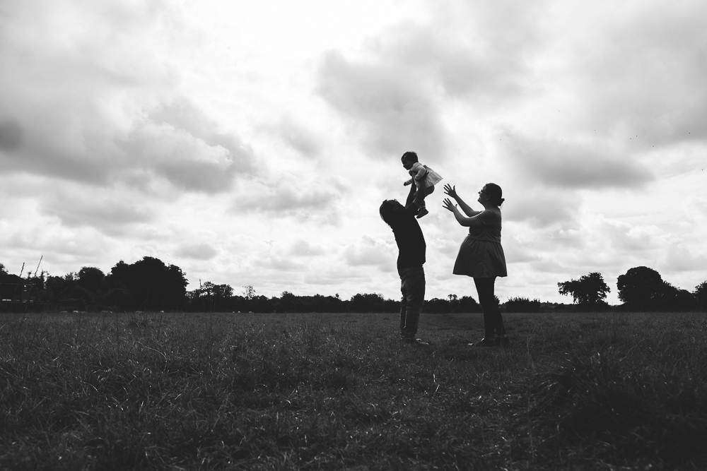 PREGNANT WOMAN AND PARTNER THROWING CHILD IN AIR IN FIELD