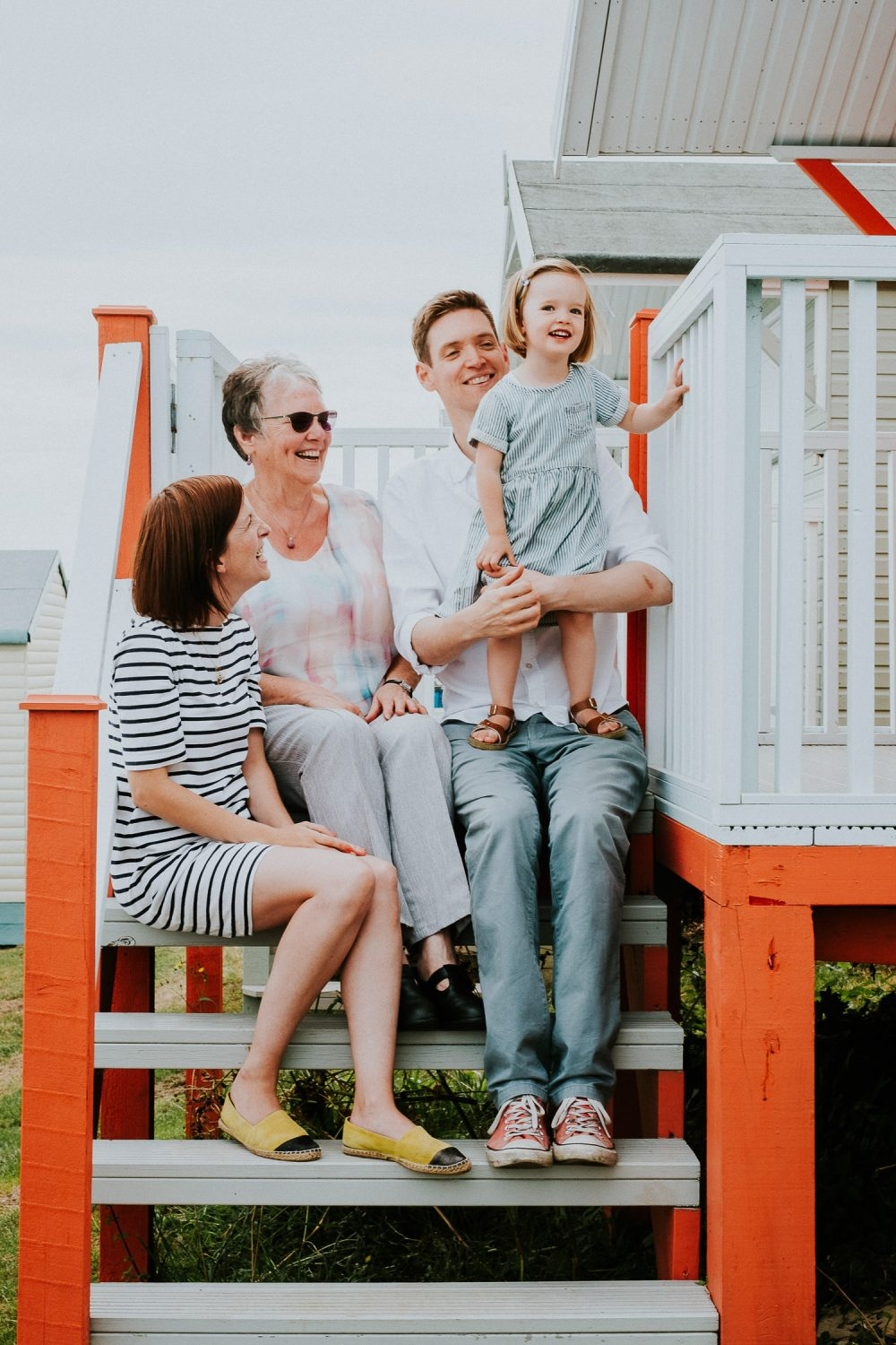 FAMILY SITTING ON BEACH HUT STEPS WHITSTABLE FAMILY PHOTOGRAPHER