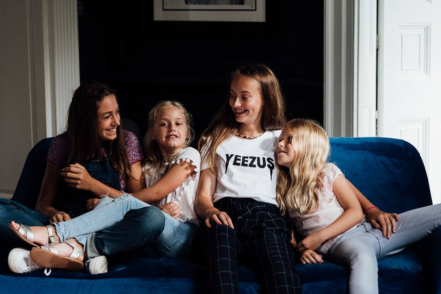 5 reasons you shouldn't wear matching outfits for your family photos. TOlder girl with younger sisters on sofa.