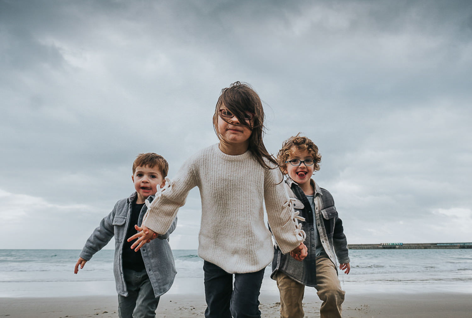 5 reasons you shouldn't wear matching outfits for your family photos. Children on the beach in Winter.