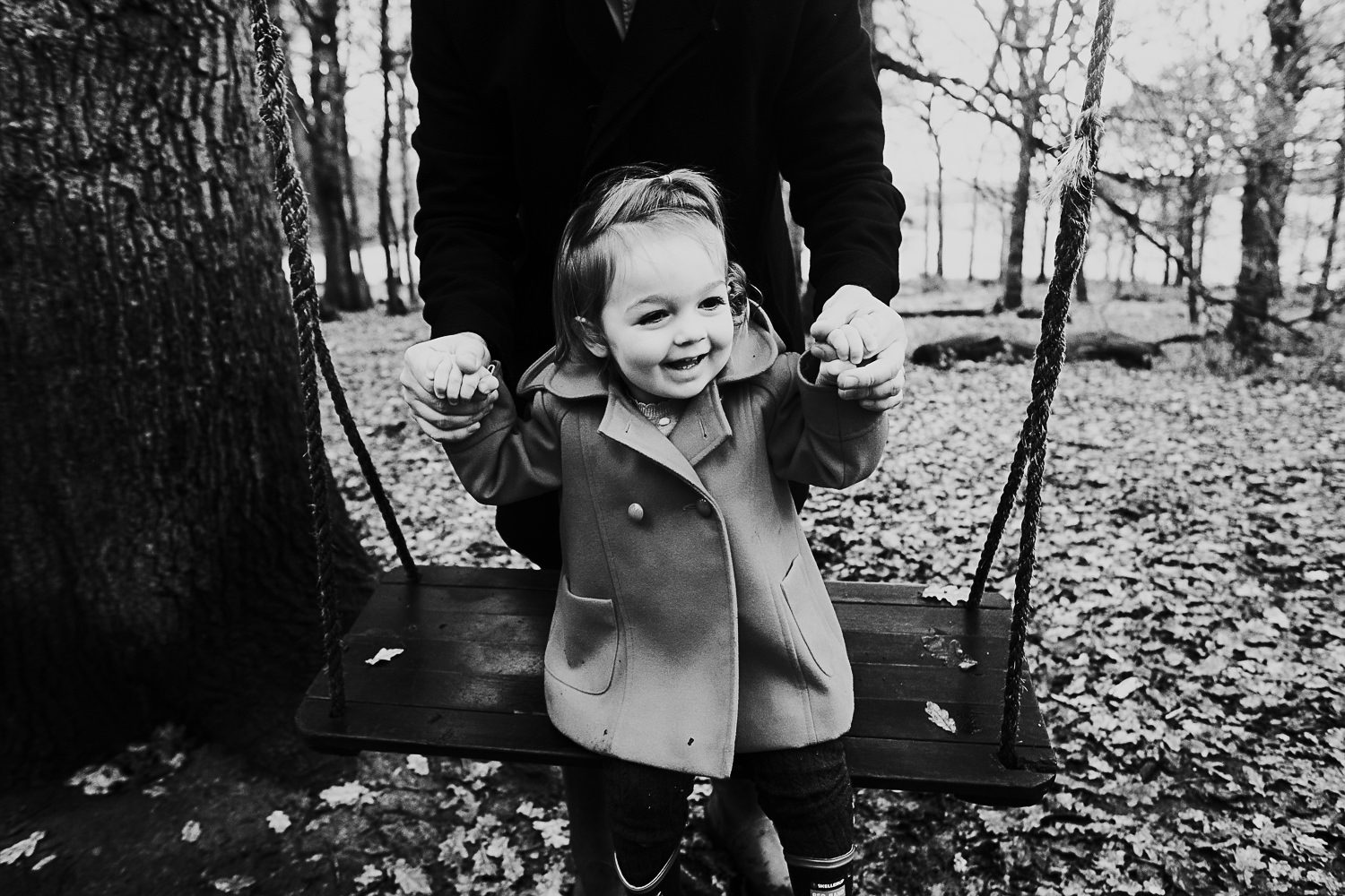 Father and daugher on swing in woods