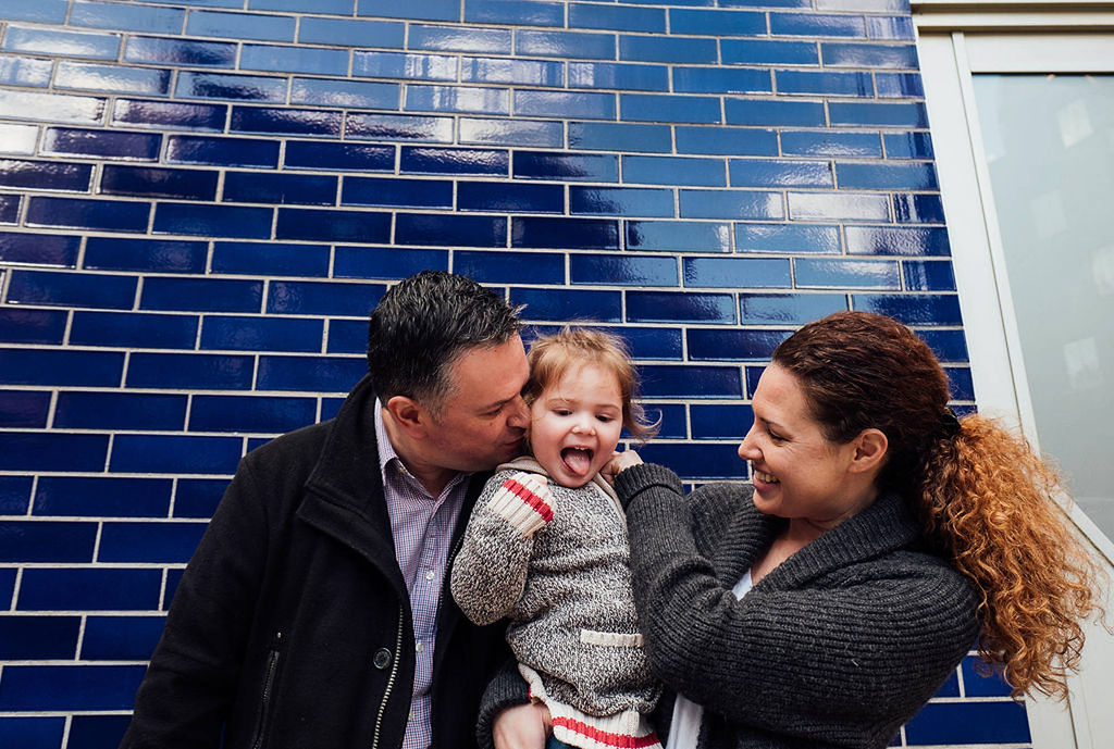 london family photographs parents with toddler in front of tiled wall