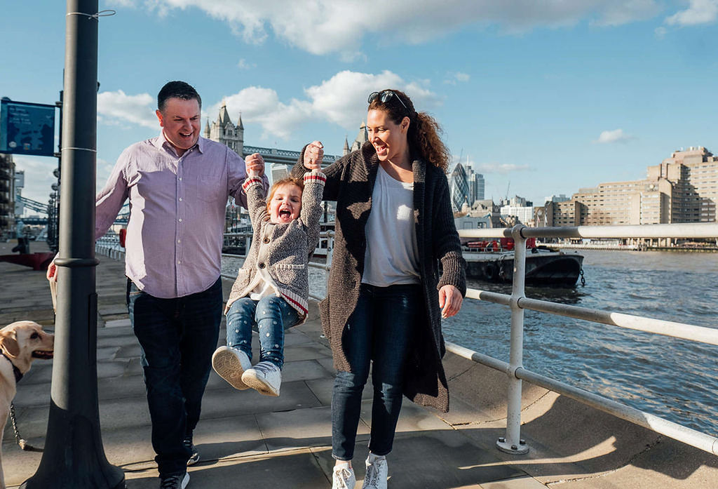 Parents swinging toddler by arms london family photographs tower bridge