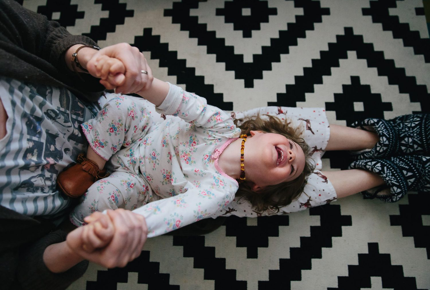 mum and daughter playing and laughing on rug