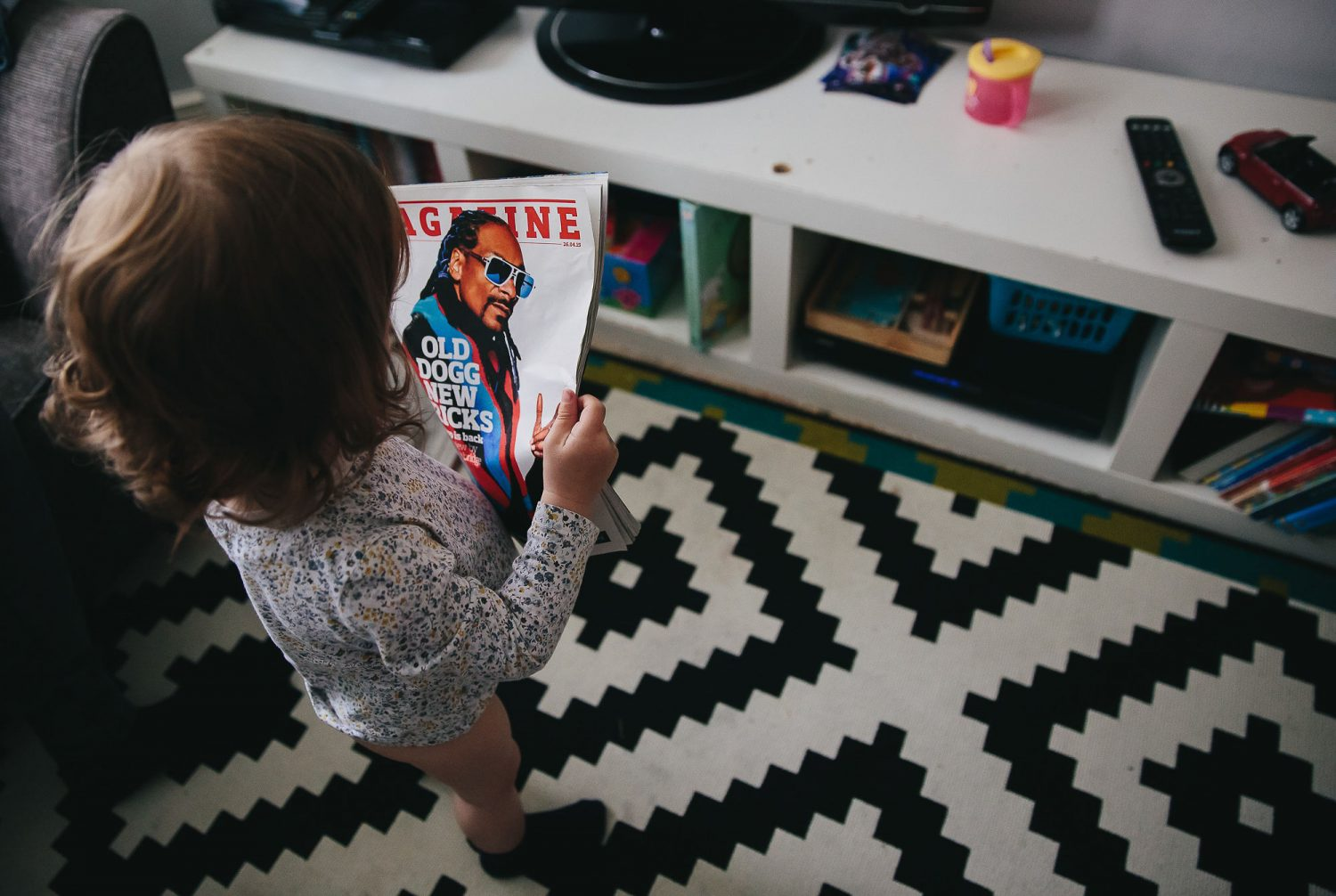 child reading a magazine with snoop dogg on the cover