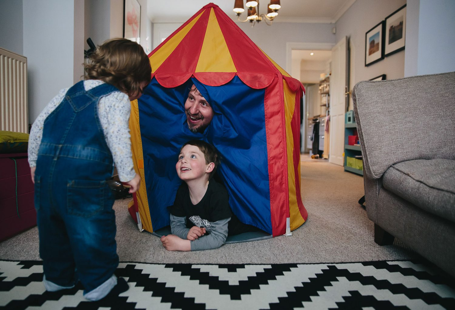 day in the life photography dad playing in tent with two young children indoors