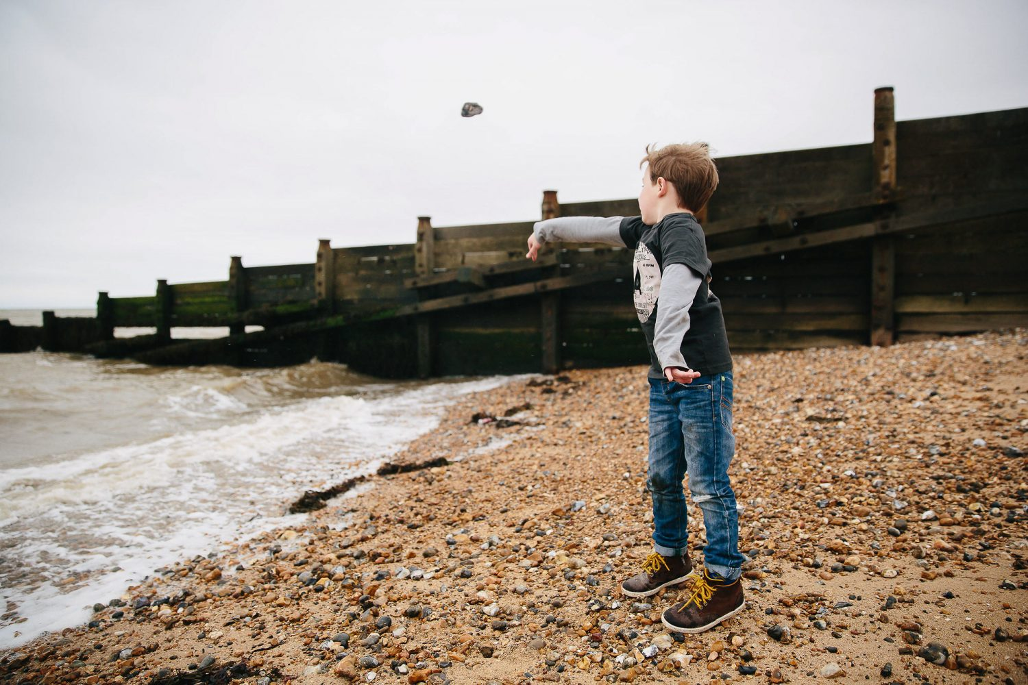 day in the life photography young boy throwing stones on beach