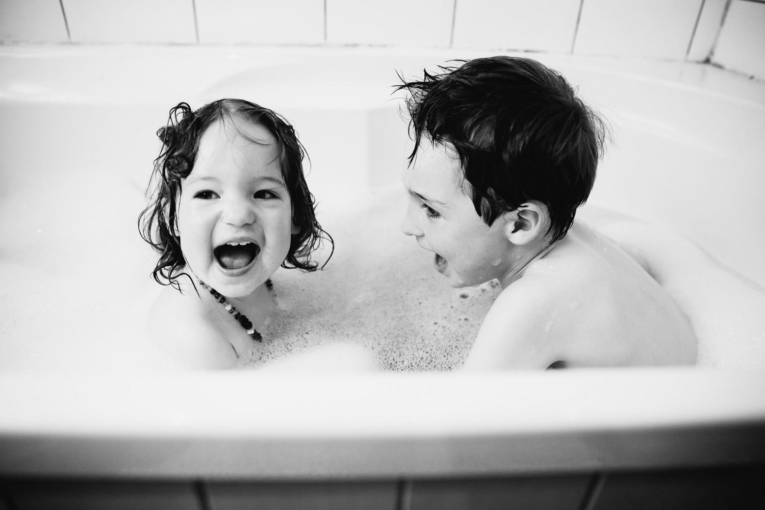 young siblings brother and sister having fun in the bath with lots of bubbles