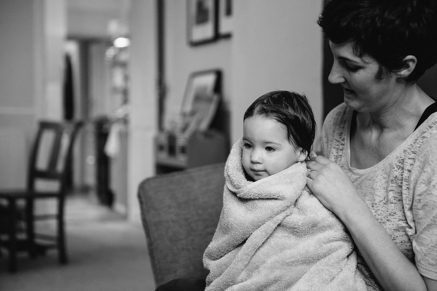 young toddler girl wrapped up in towel with her Mum black and white image