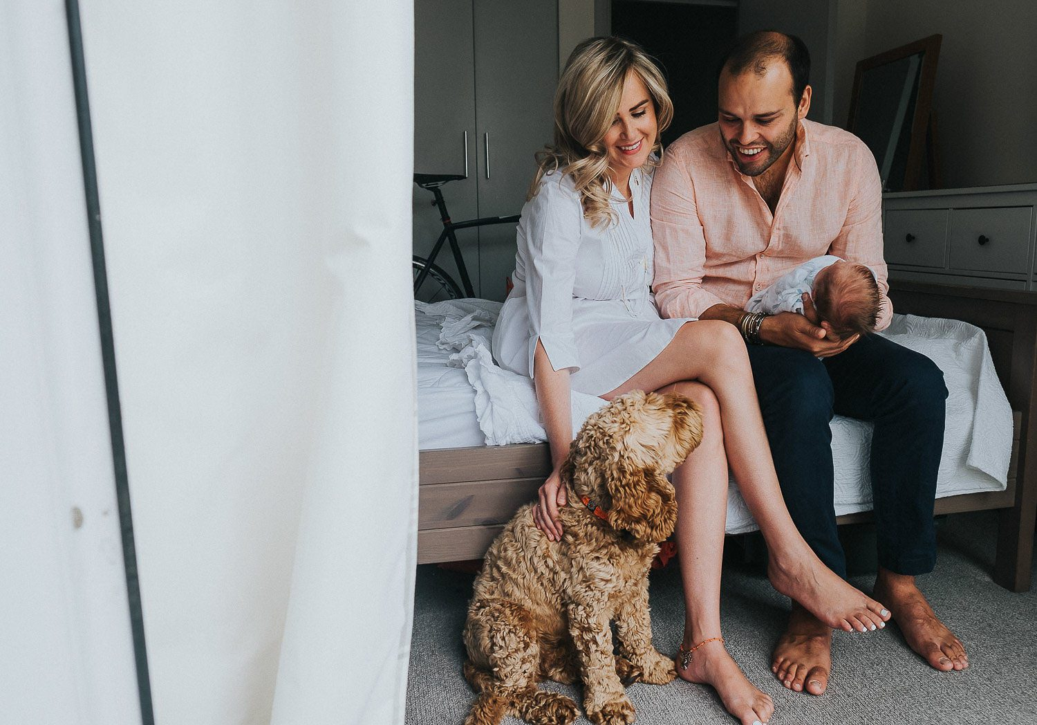 Newborn photo shoot at home, new parents with dog and baby