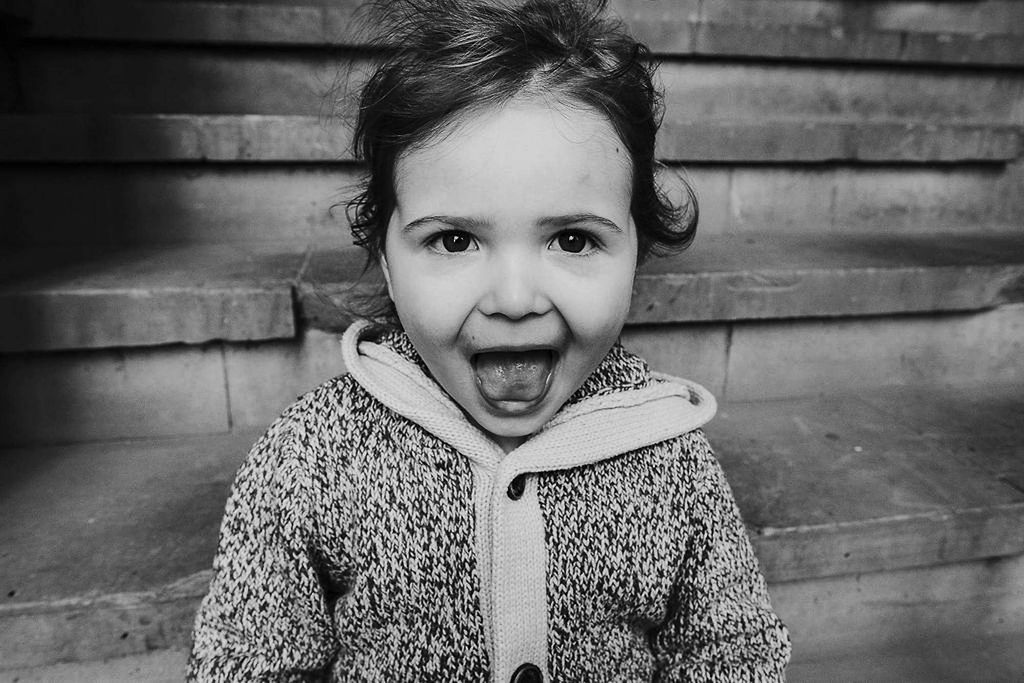 black and white photo of toddler girl sticking tongue out