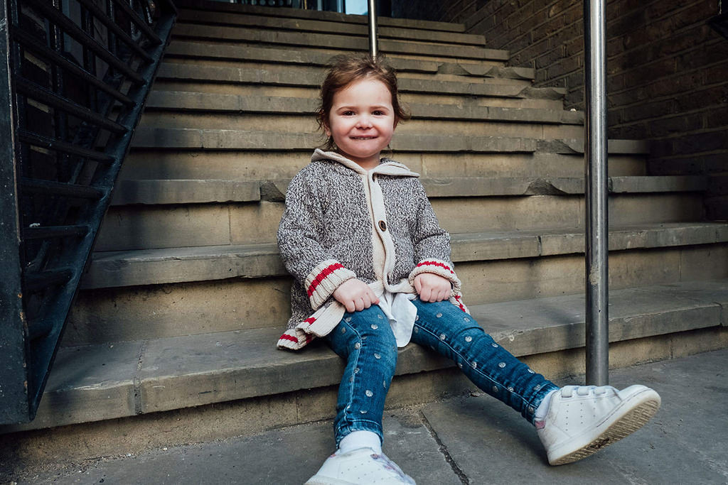 toddler girl sitting on steps in London