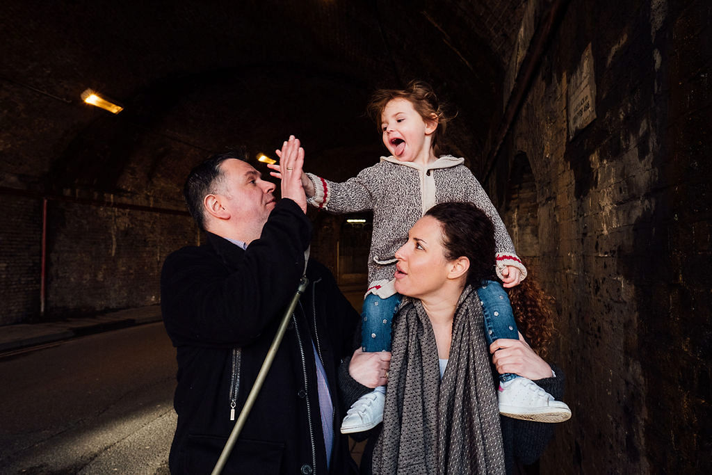 London family photographs parents with toddler in tunnel