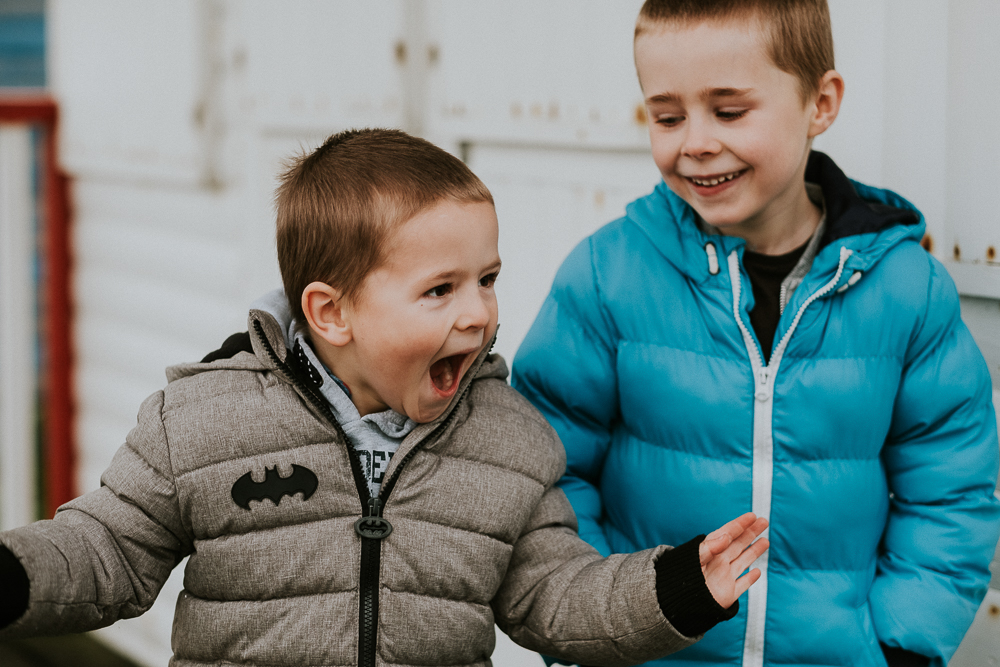 Two boys playing and laughing in winter coats. Kent Christmas Mini Photo Shoots.