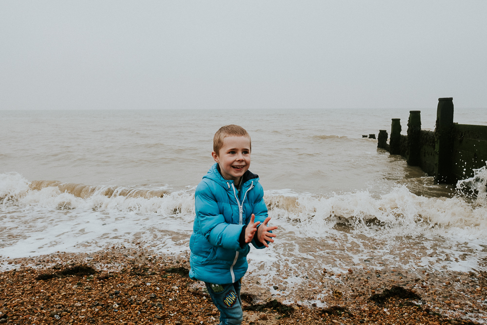 Boy playing on beach at Tankerton Whitstable. Kent Christmas Mini Photo Shoots