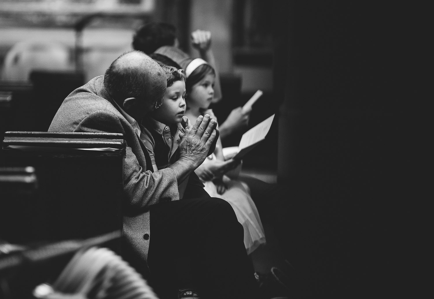 black and white small boy praying in church london christening photography