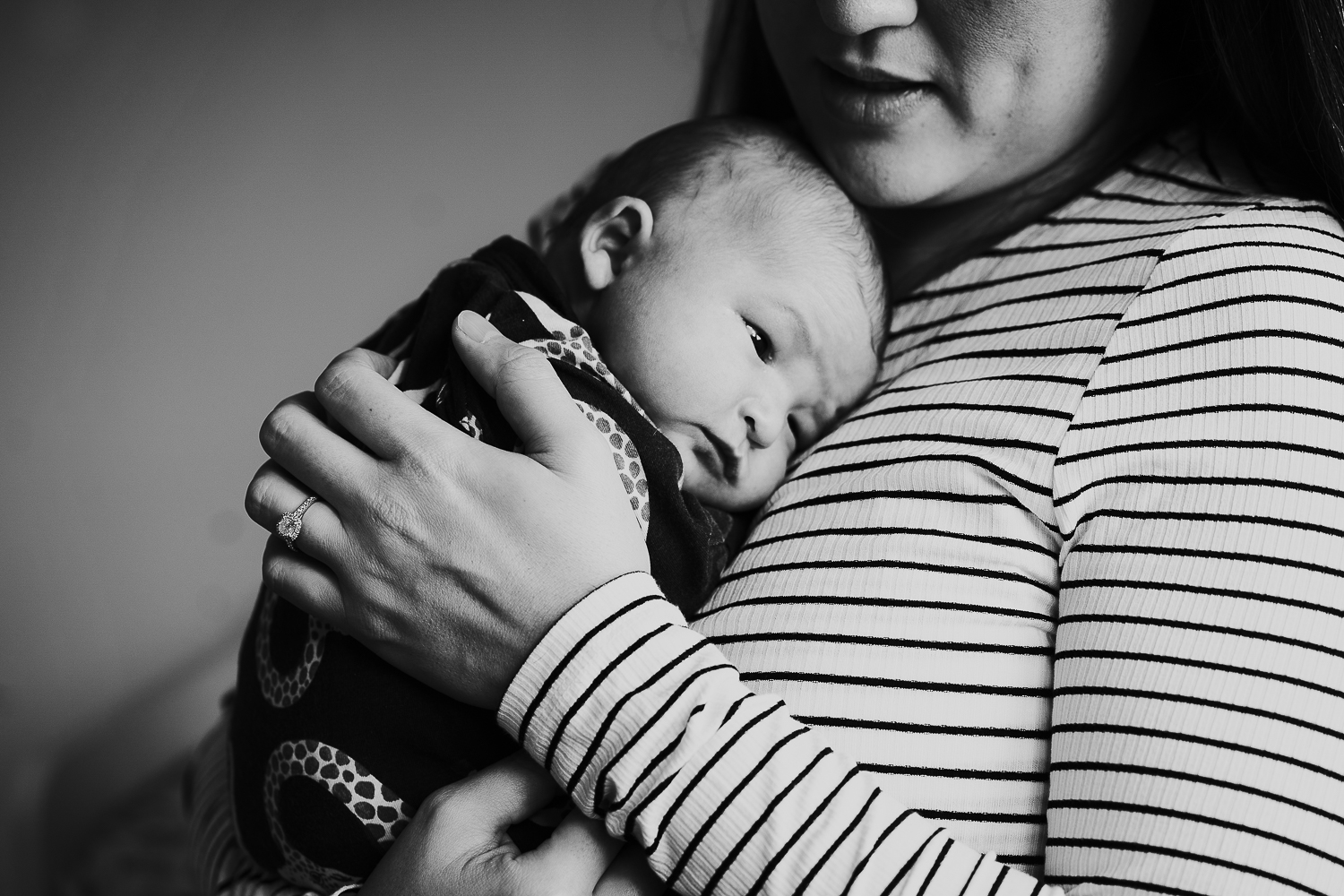 baby sleeping on mother during photo session at home