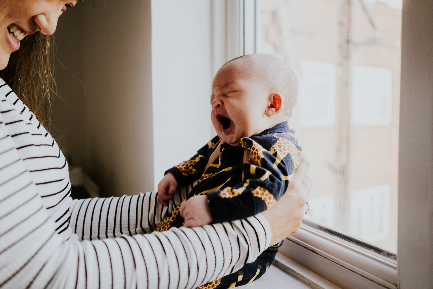 newborn baby yawning sat in window