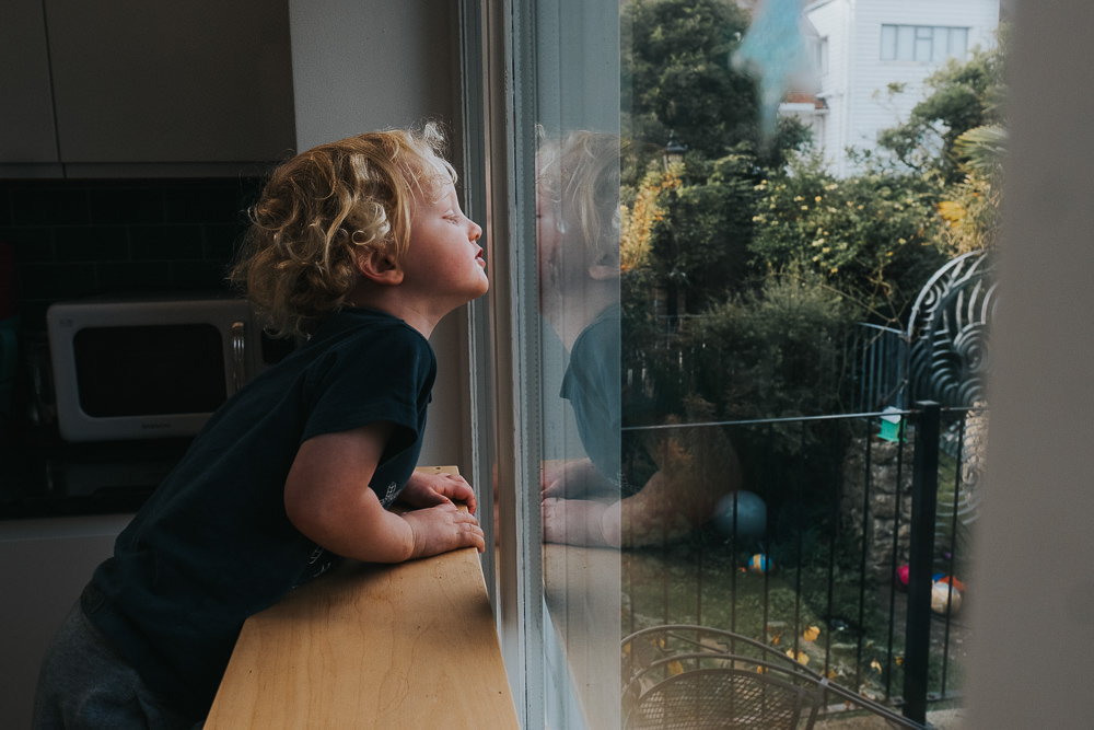 KIDS CORONAVIRUS LOCKDOWN CHILD LOOKING OUT OF WINDOW