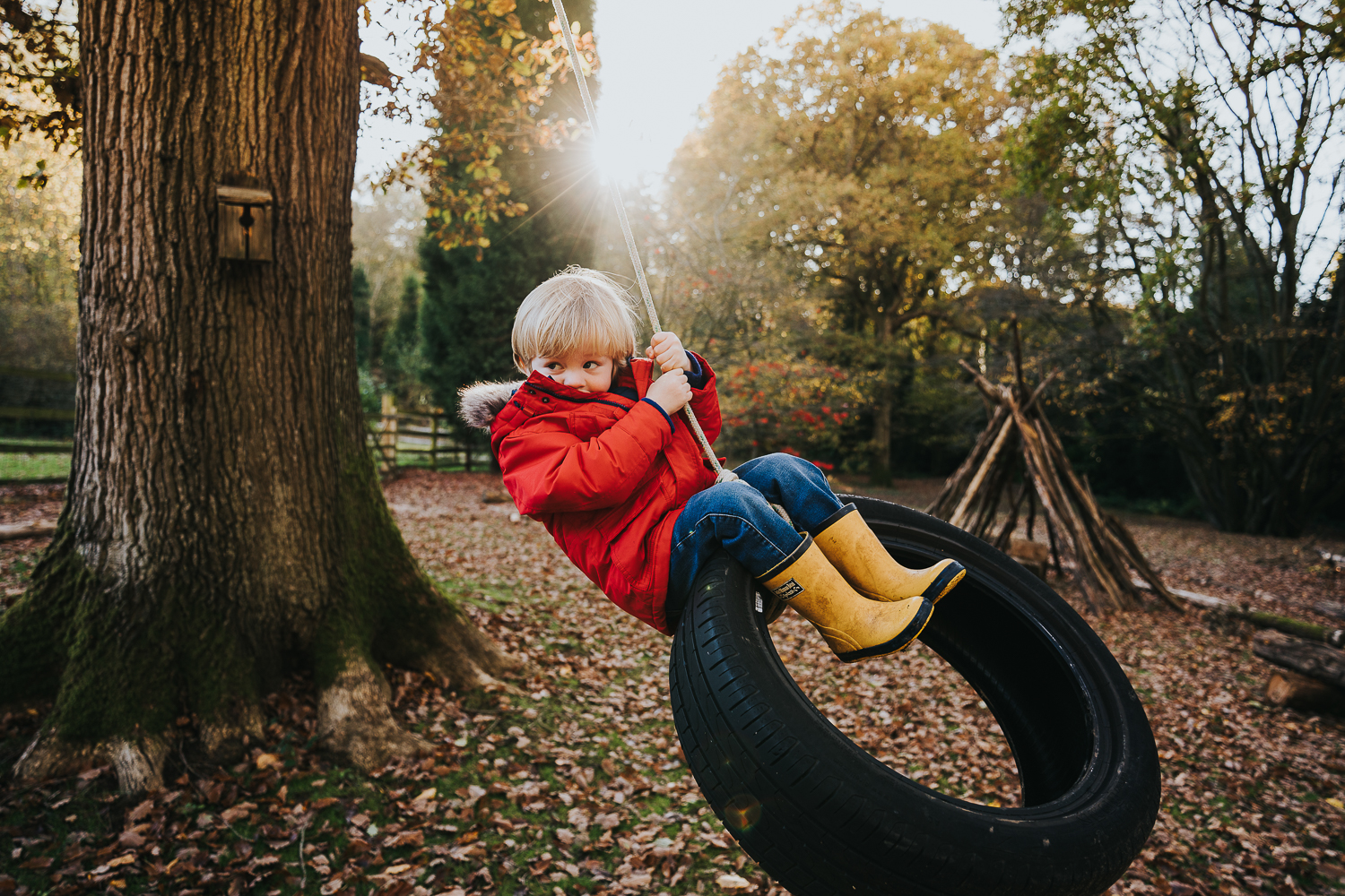 London family photography 2020 young boy swinging on tyre swing in autumn sunshine