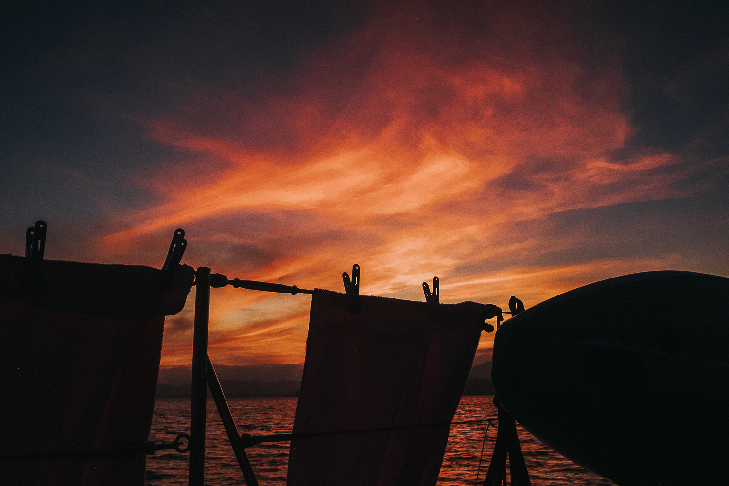 Thailand sunset shilhouette of towels on boat in front of orange sky