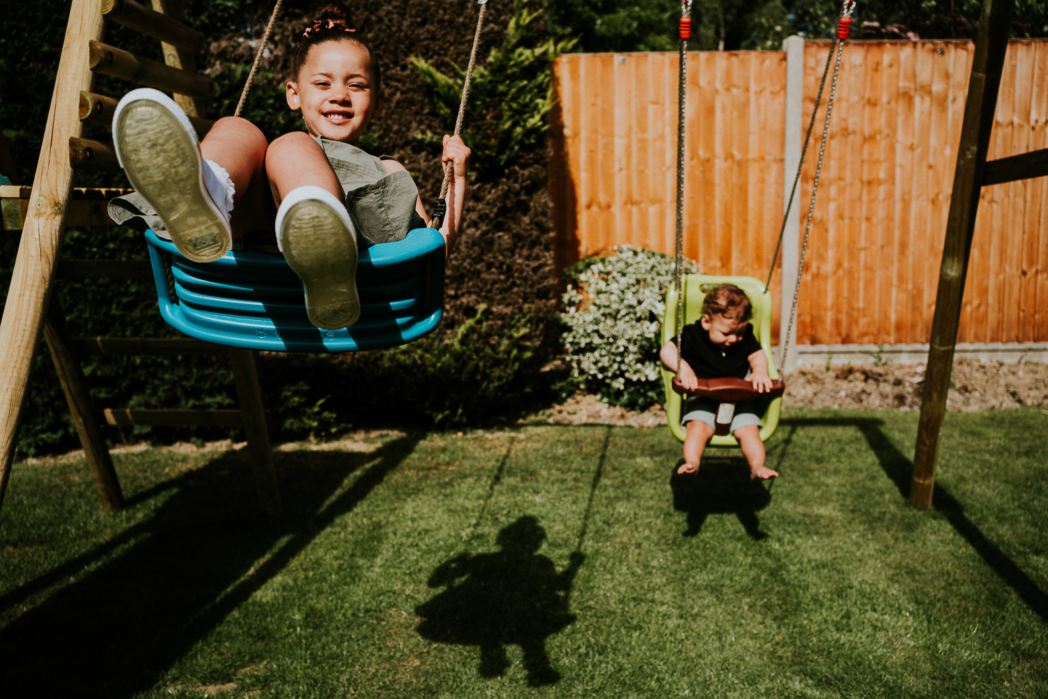 London family photography 2020 siblings on swings in garden in the sunshine