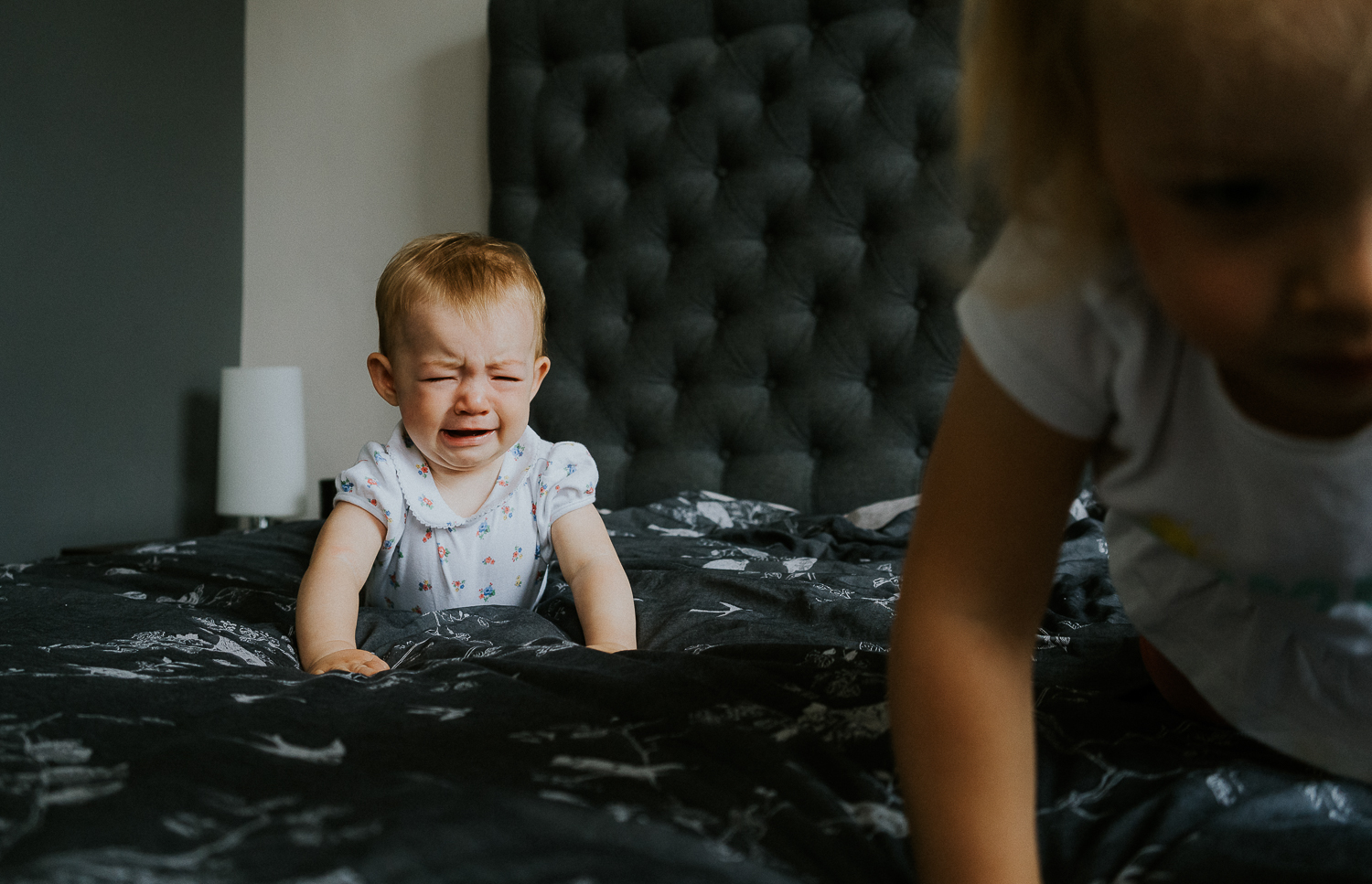 family photography 2020 baby crying on bed whilst siblings crawls away