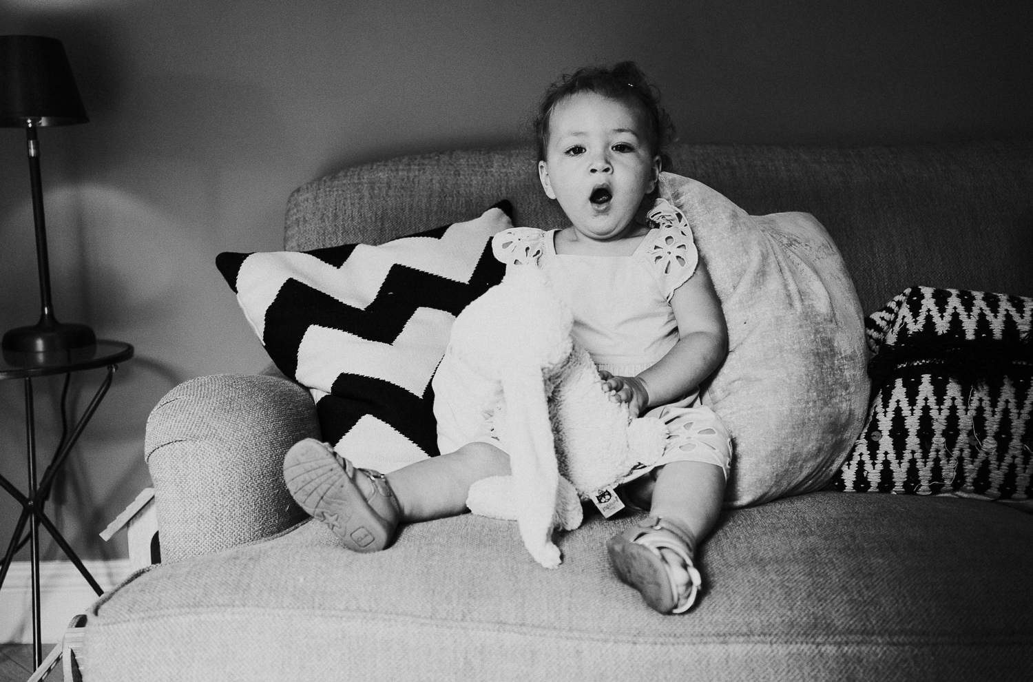 sibling family photography 2020 black and white portrait young girl on sofa yawning