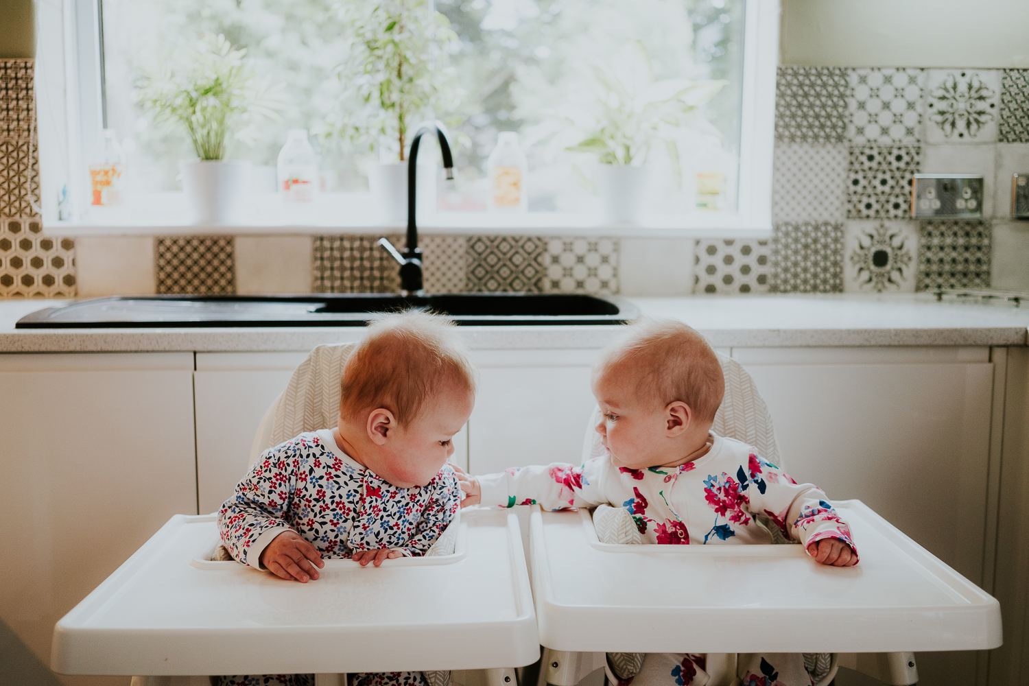 day in the life photo shoot twin baby girls in matching highchairs in kitchen