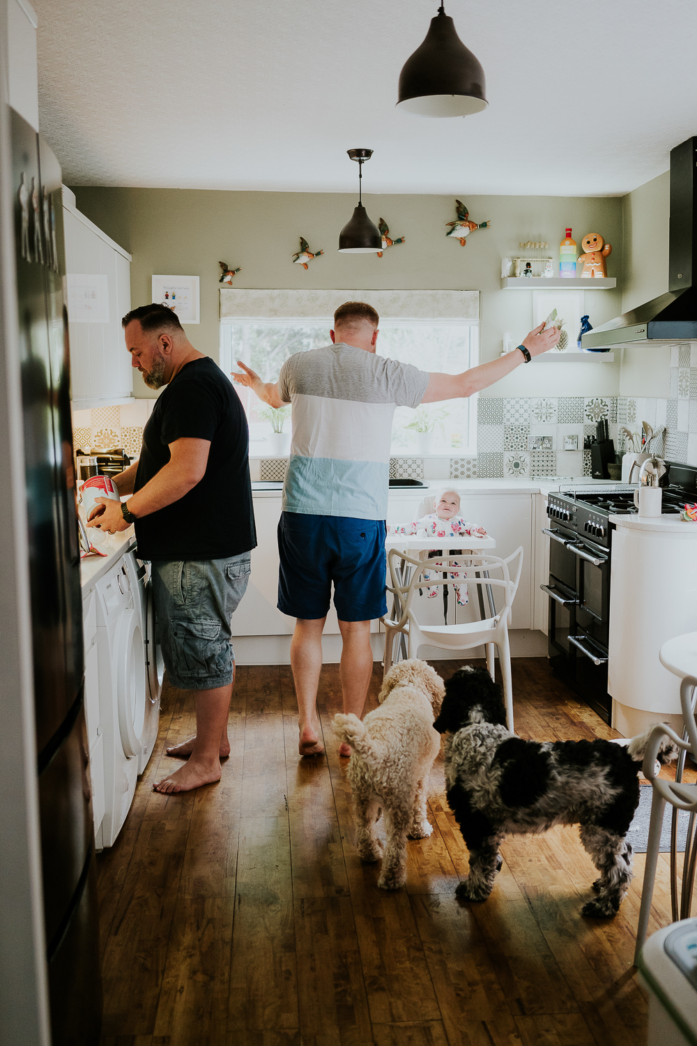 day in the life photo shoot two dads with baby twin girls in kitchen family scene
