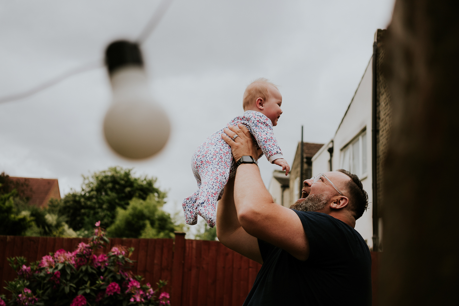 day in the life photo shoot father holding baby daughter in the air grey clouds behind