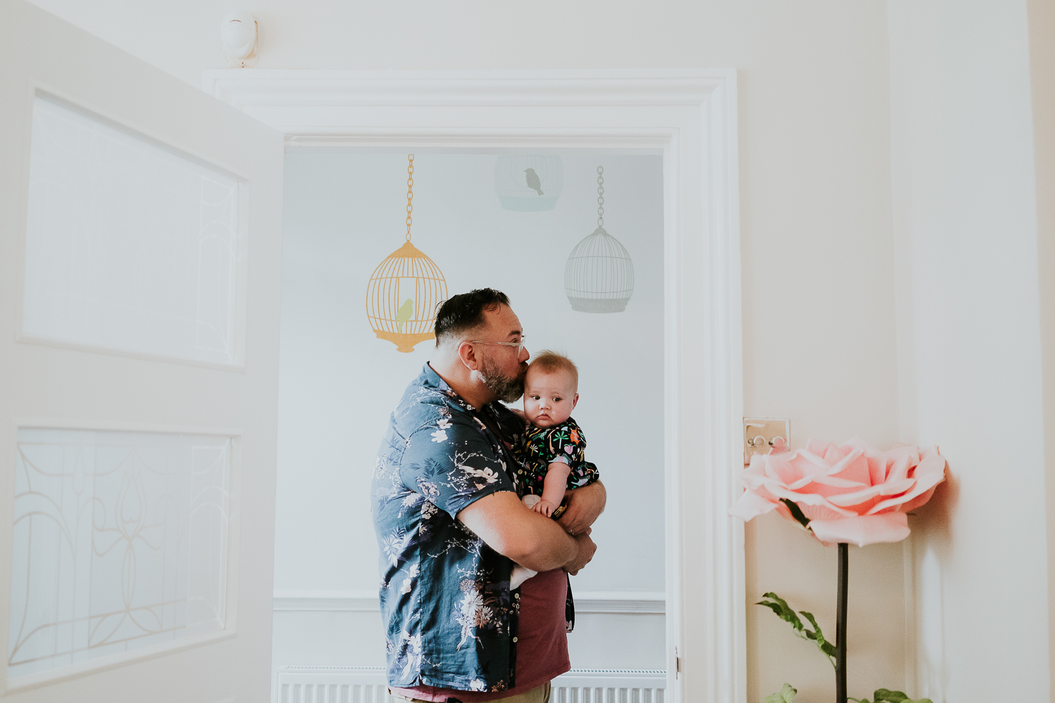 day in the life photo shoot father holding baby daughter in hallway kissing her on the head