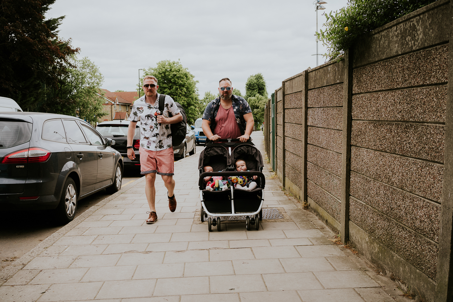 day in the life photo shoot two dads walking along pavement pushing a double buggy with two baby girls