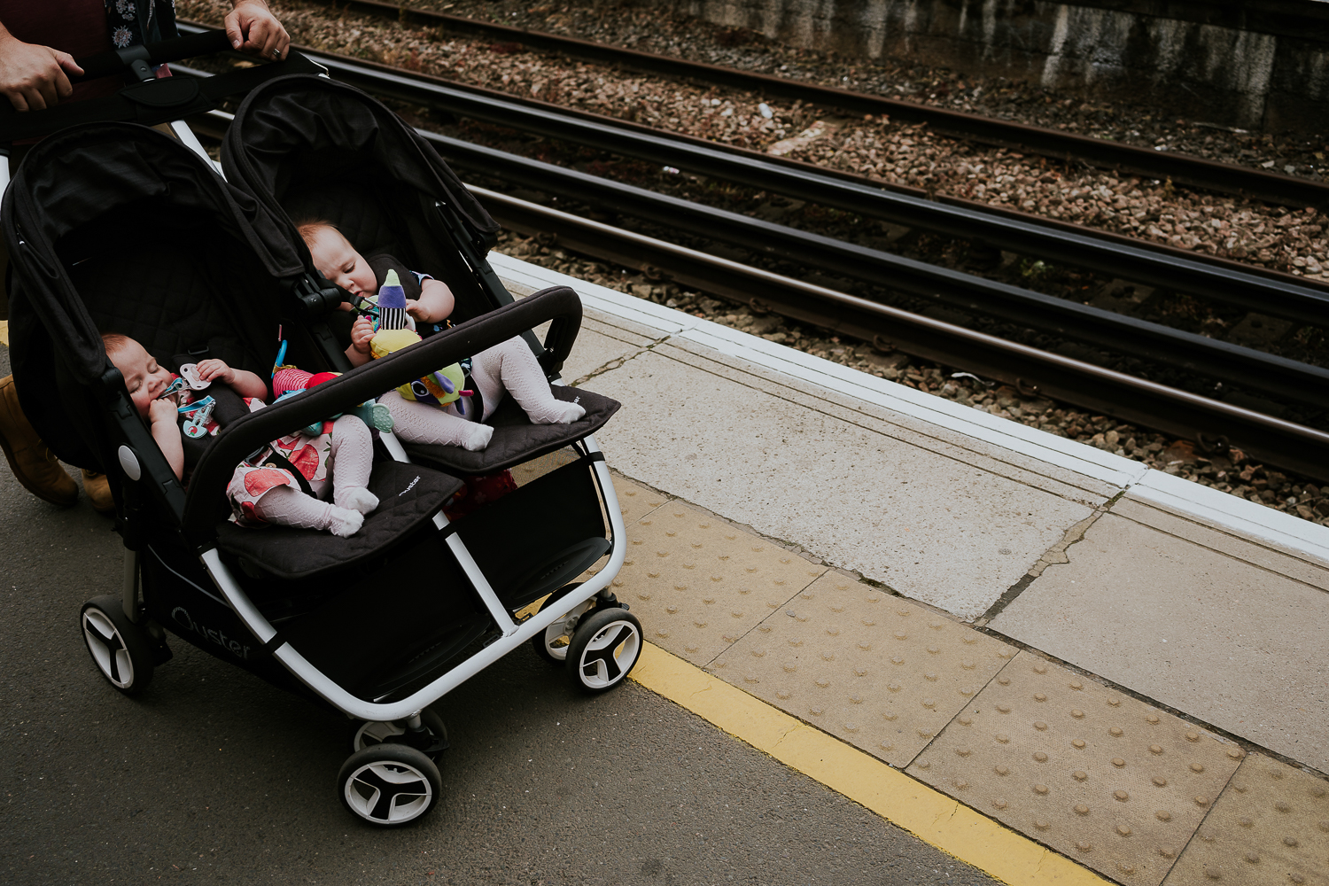 day in the life photo shoot twin baby girls in double pushchair on train platform