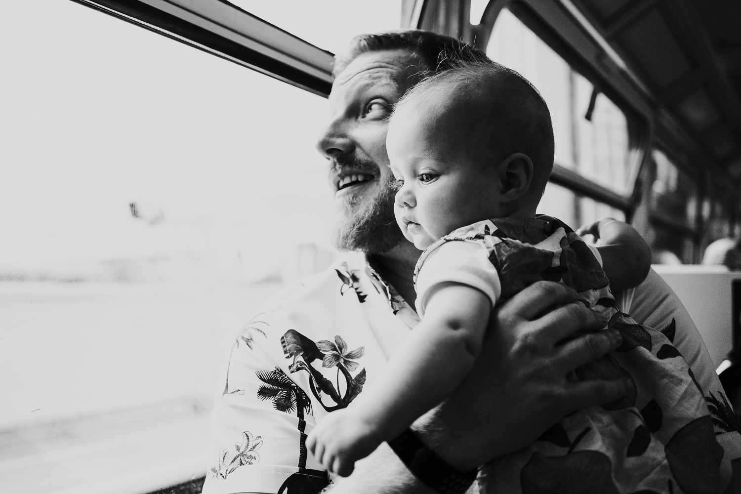 day in the life photo shoot father and baby girl on train black and white shot looking out of window