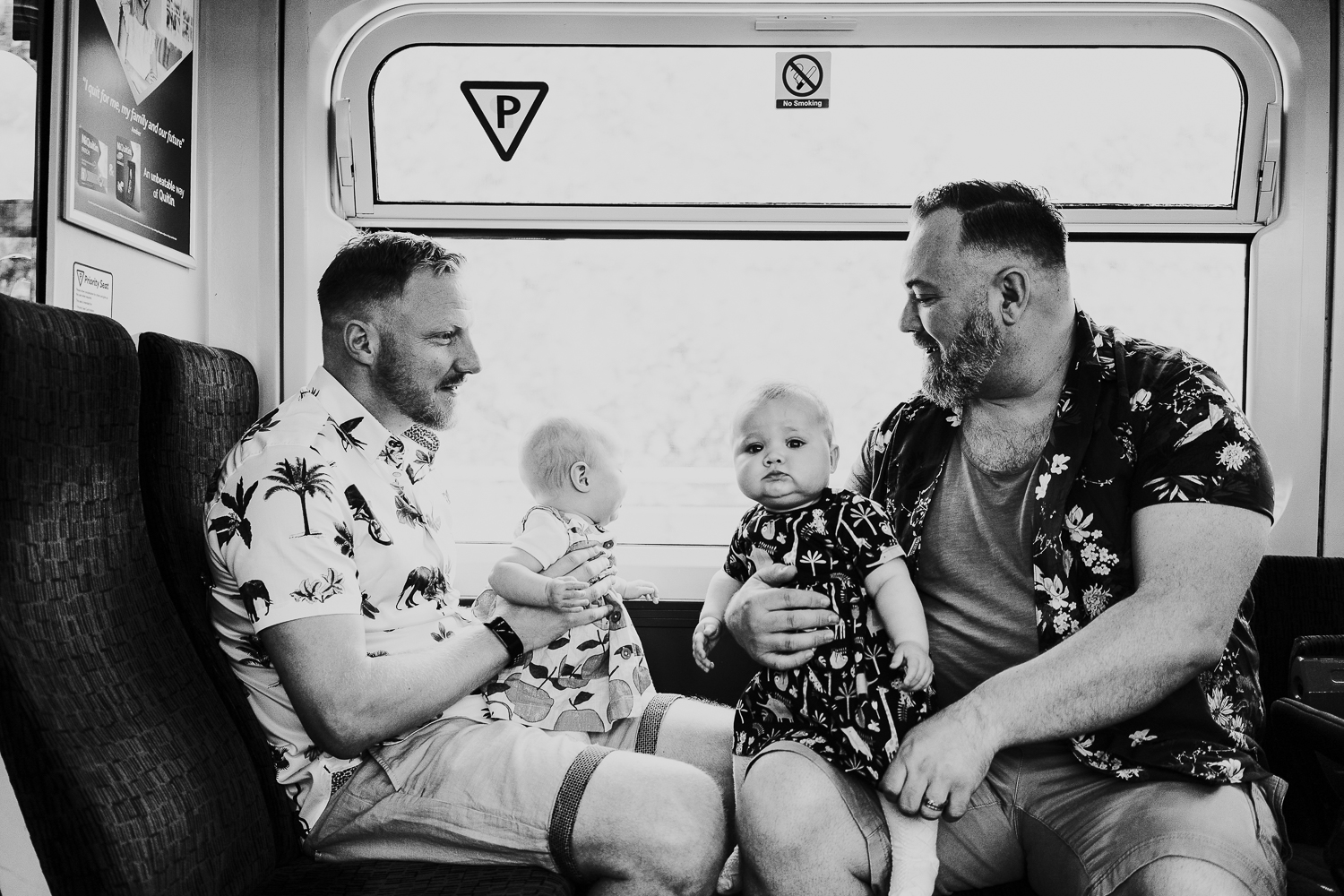day in the life photo shoot two fathers and twin baby girls on train black and white shot