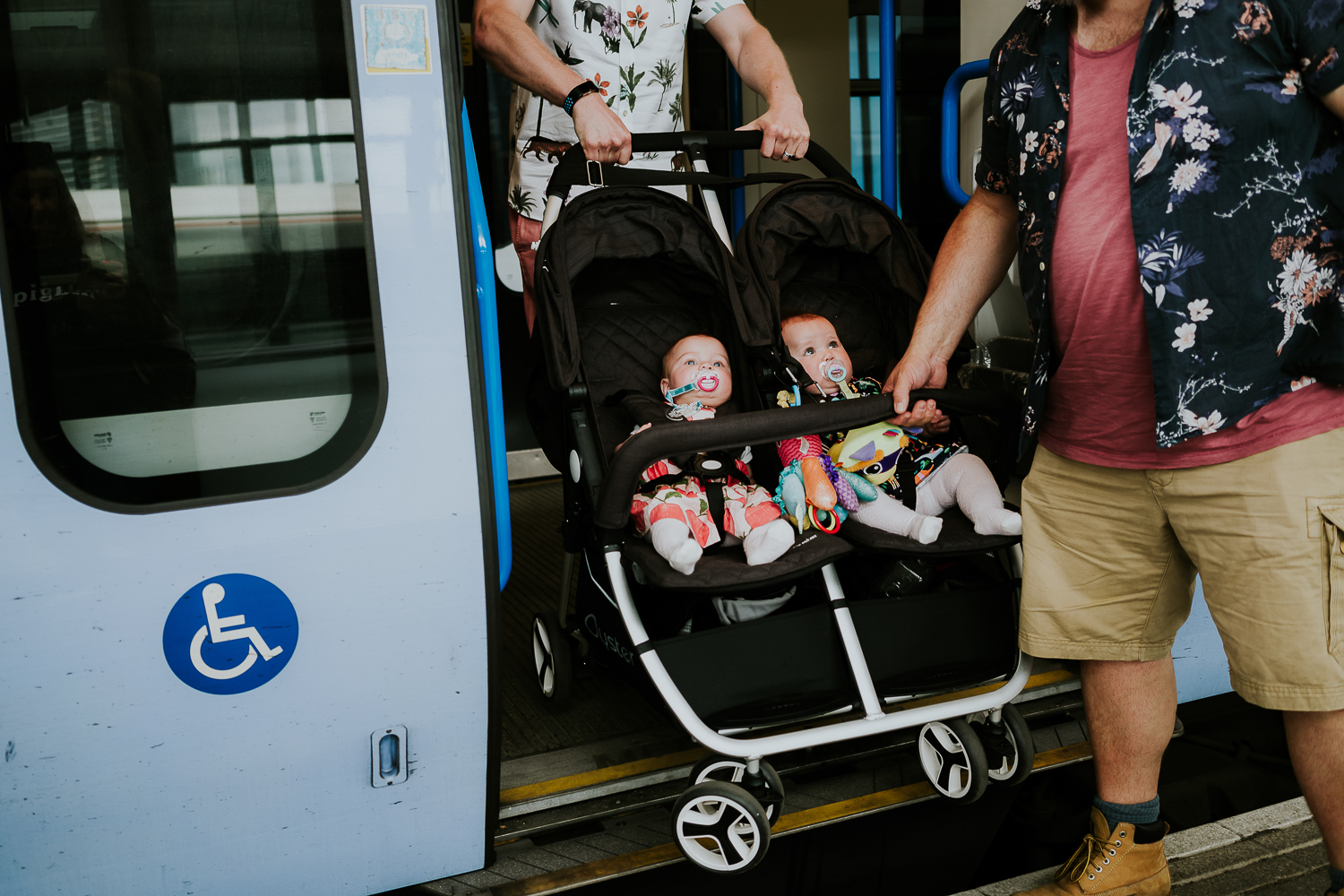 day in the life photo shoot two fathers and twin baby girls in double buggy getting off train