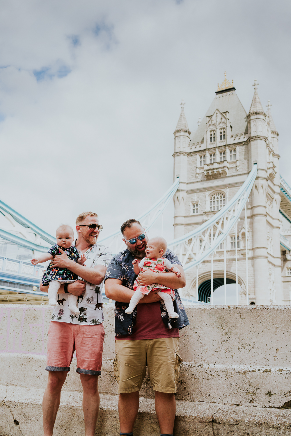 day in the life photo shoot two dads with twin baby girls standing with view of Tower Bridge in background