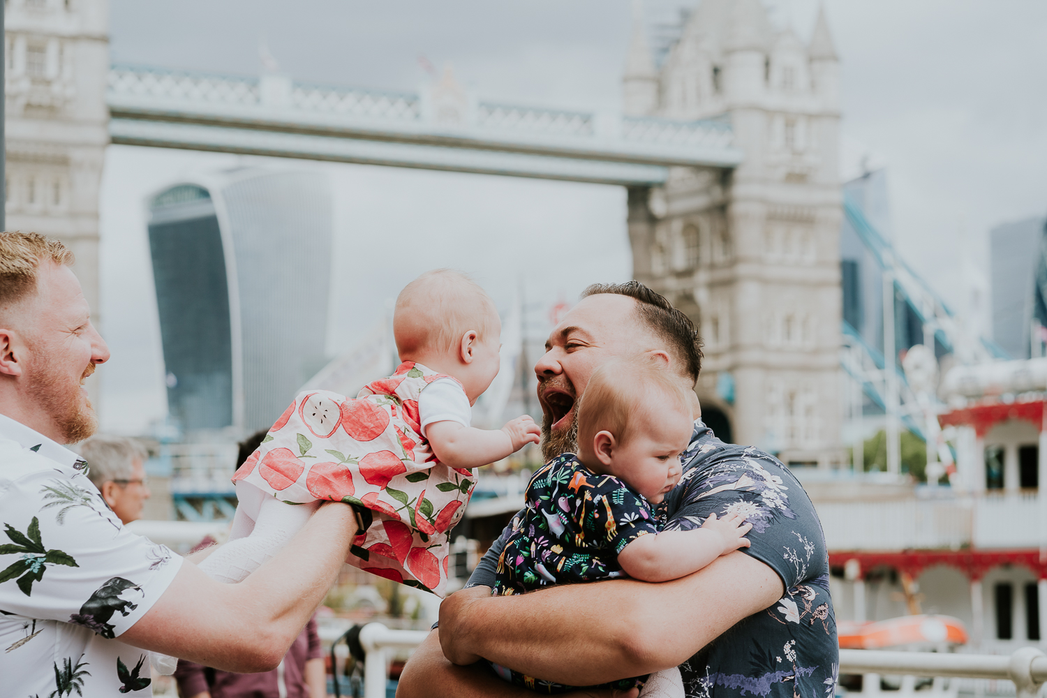 day in the life photo shoot two dads with twin baby girls playing with view of Tower Bridge in background