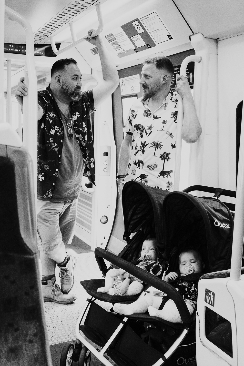 day in the life photo shoot two dads standing on train with double pushchair with twin baby girls