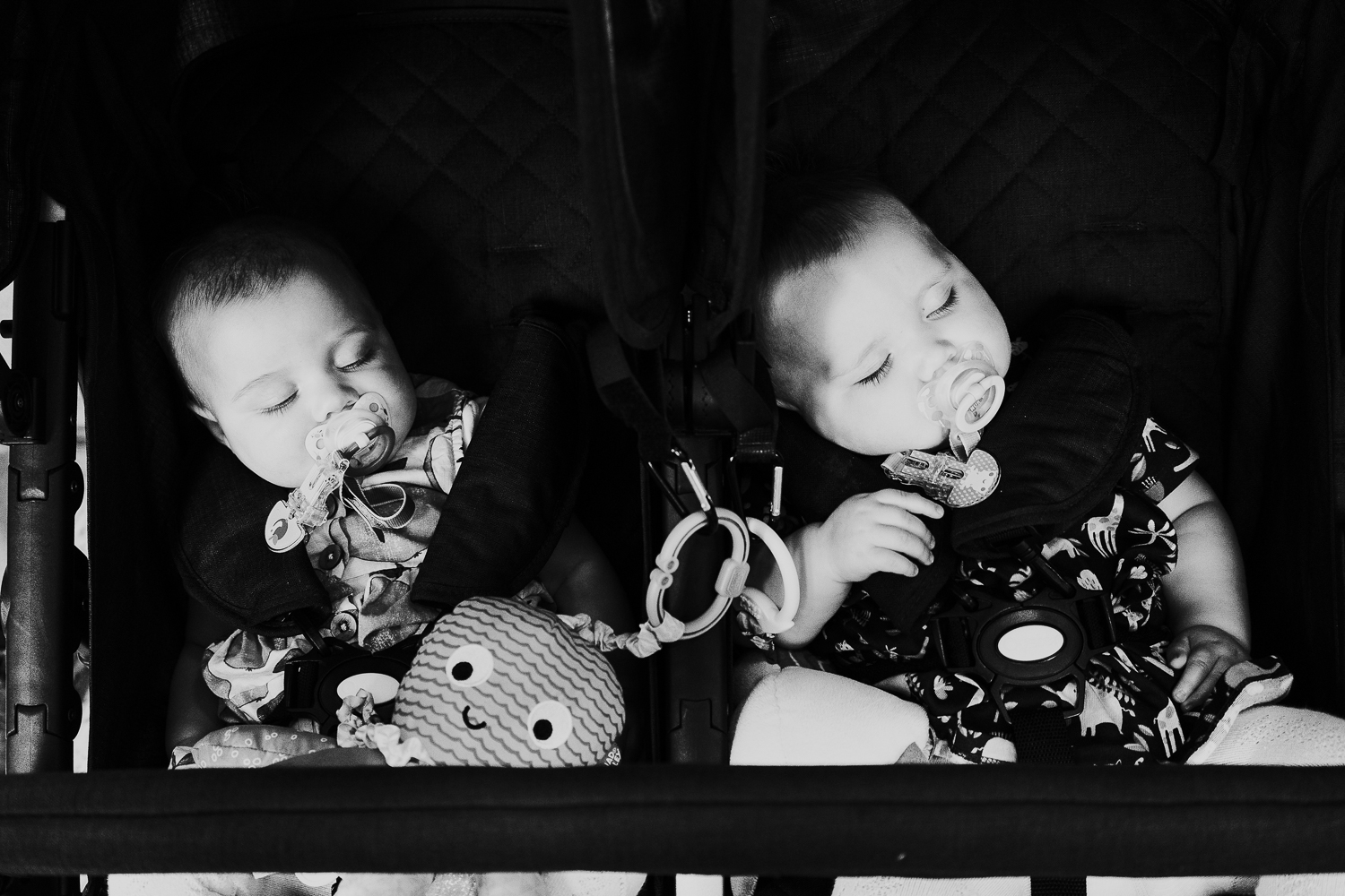 day in the life photo shoot twin baby girls asleep in double pushchair with dummies black and white shot