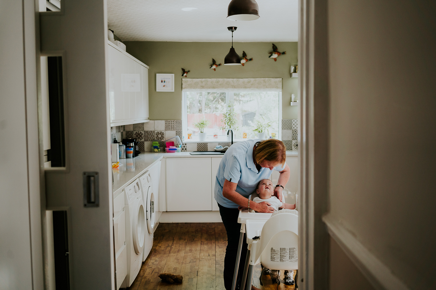 day in the life photo shoot kitchen scene with older woman strapping baby into a highchair