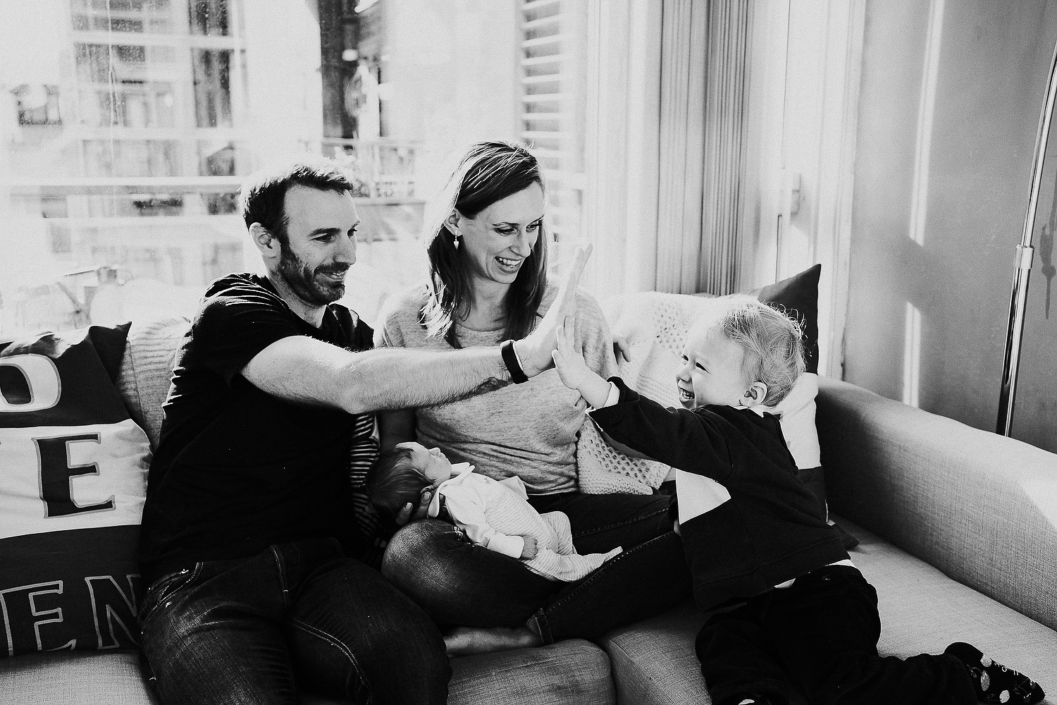 east london newborn photographer mother, father, little boy and newborn baby on sofa