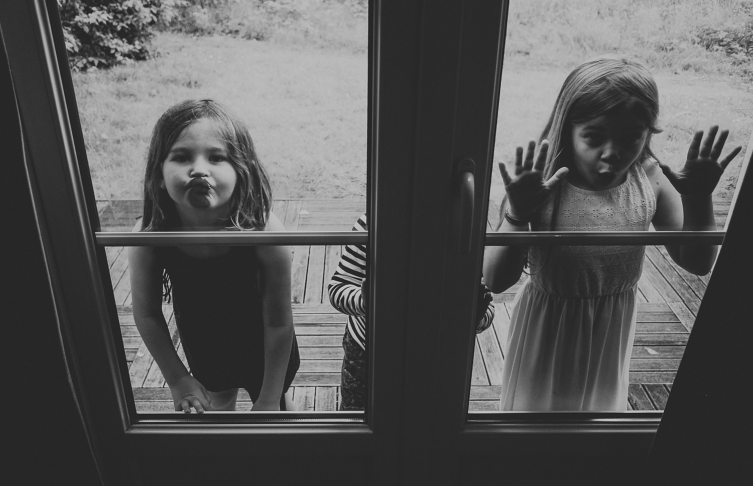 TWO CHILDREN PRESSING FACES ON WINDOW GLASS FAMILY PHOTOGRAPHY AT CENTER PARCS FRANCE LAC D'AILETTE